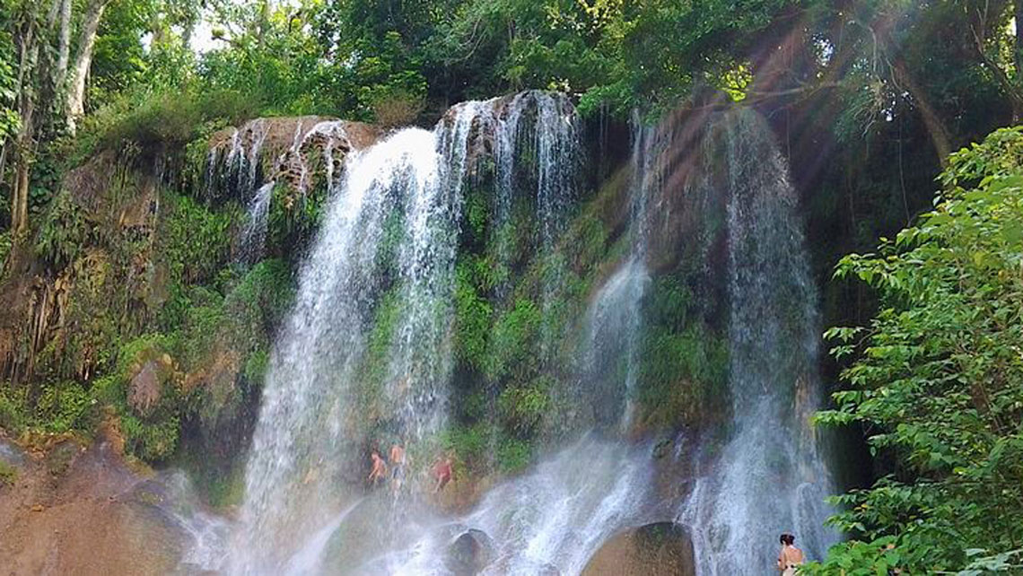 Small group of people refreshing in a beautiful waterfall