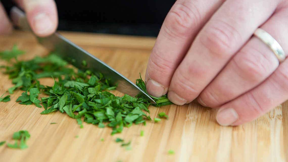 A person chopping chives for cooking