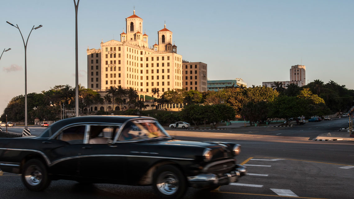 Old American car cruising on the Malecon Avenue near Nacional de Cuba Hotel