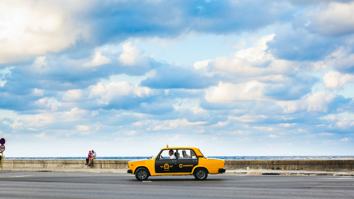 A taxi drives along Havana's famous malecon
