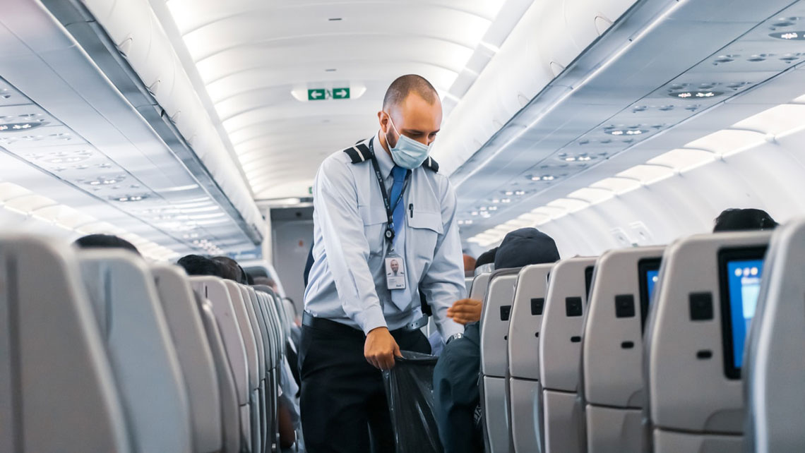 A flight attendant wearing a facemak works onboard