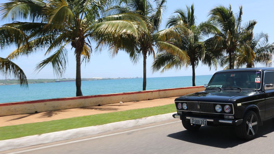 A Russian Lada car travels along a seawall in Cuba