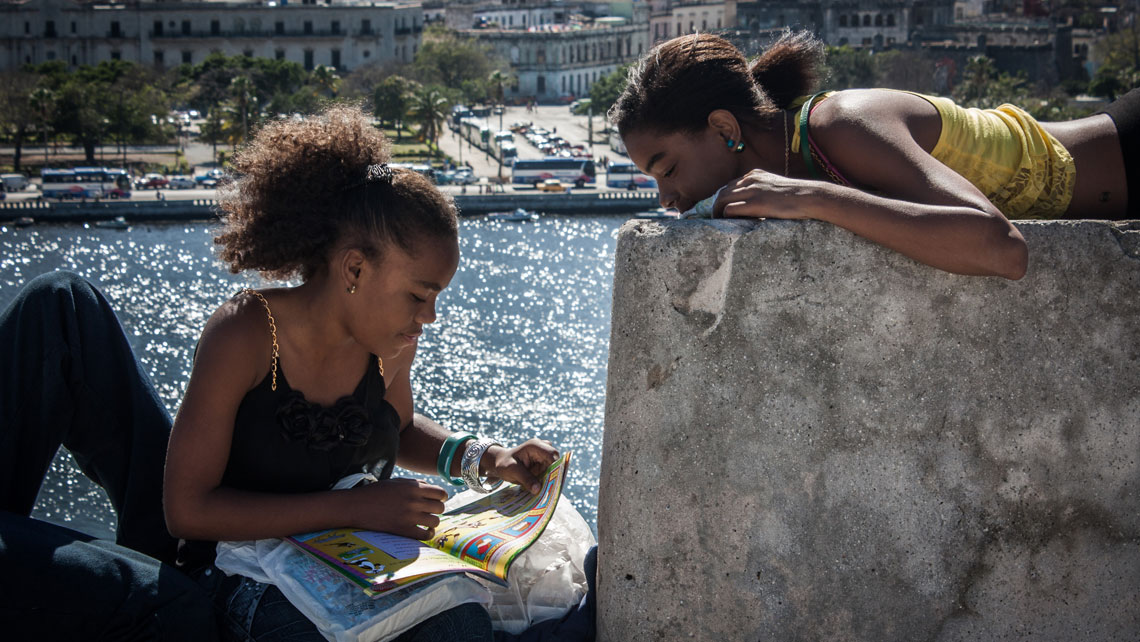 Two young Cuban girls reading a book on a wall in Havana