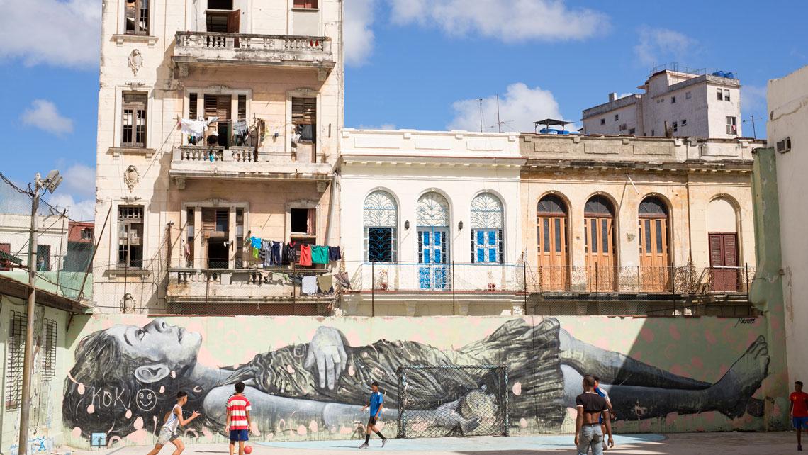 Children play next to a graffiti in Havana, Cuba