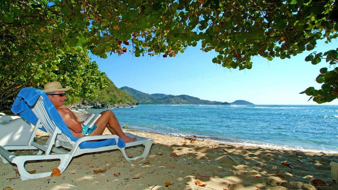 Tourist relaxes on an empty beach in Holguin reading a book