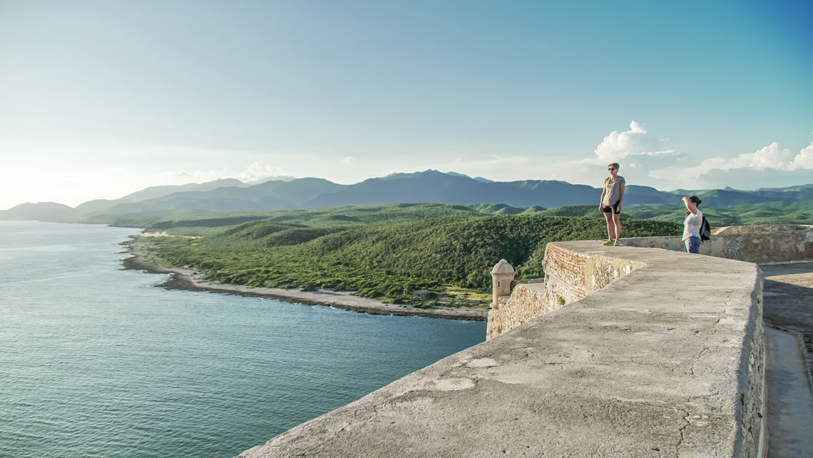 Two young women enjoying the beautiful view of the sea and the mountains from El Morro fortress in Santiago de Cuba