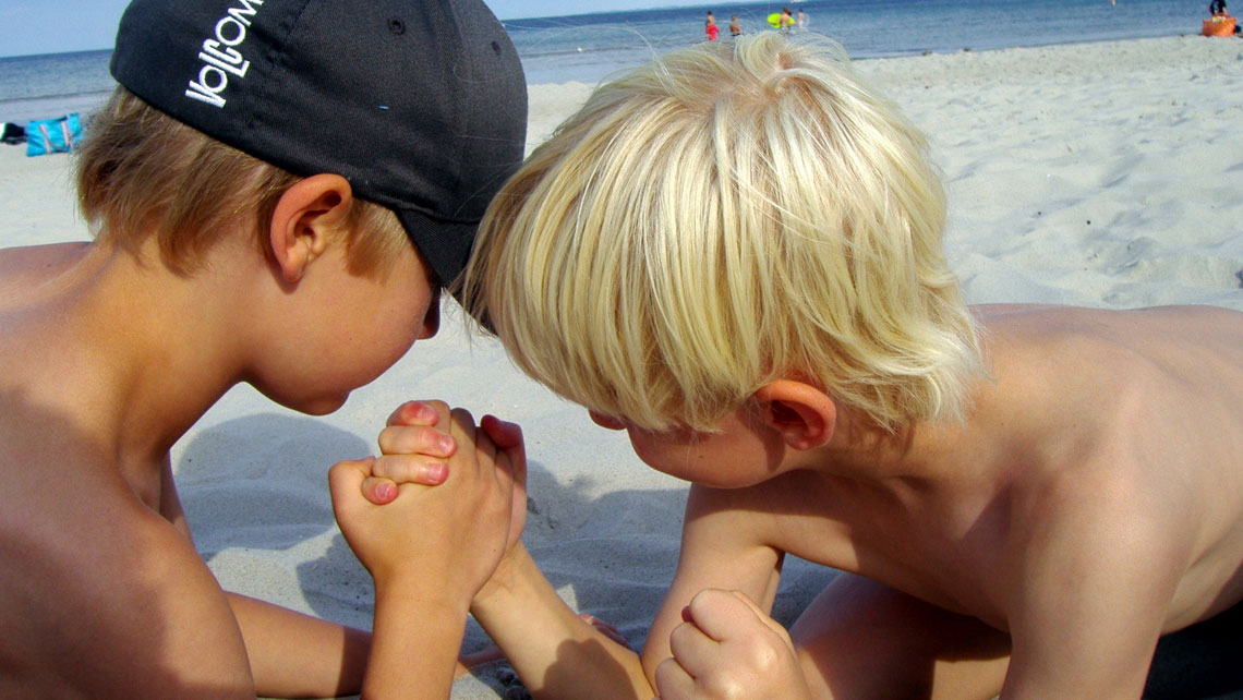 Two kids playing arm wrestling on a sandy beach