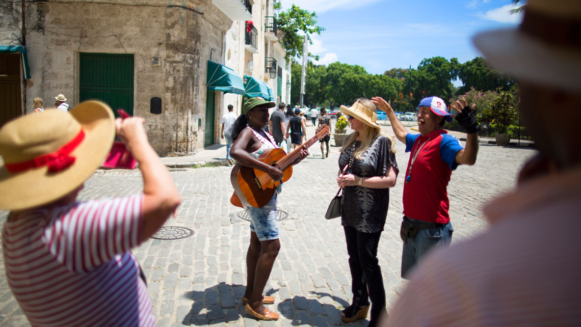 A singer and a musician entertain tourists walking through the streets of Havana