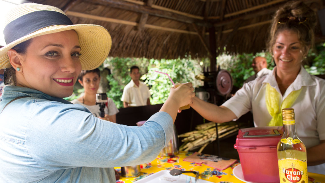 A local woman handing a beverage to a tourist possing for the photo