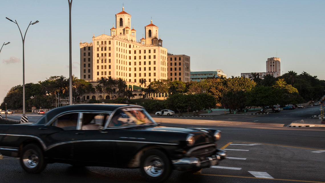 Vintage car cruising on Malecon waterfront in front of Hotel Nacional in Havana