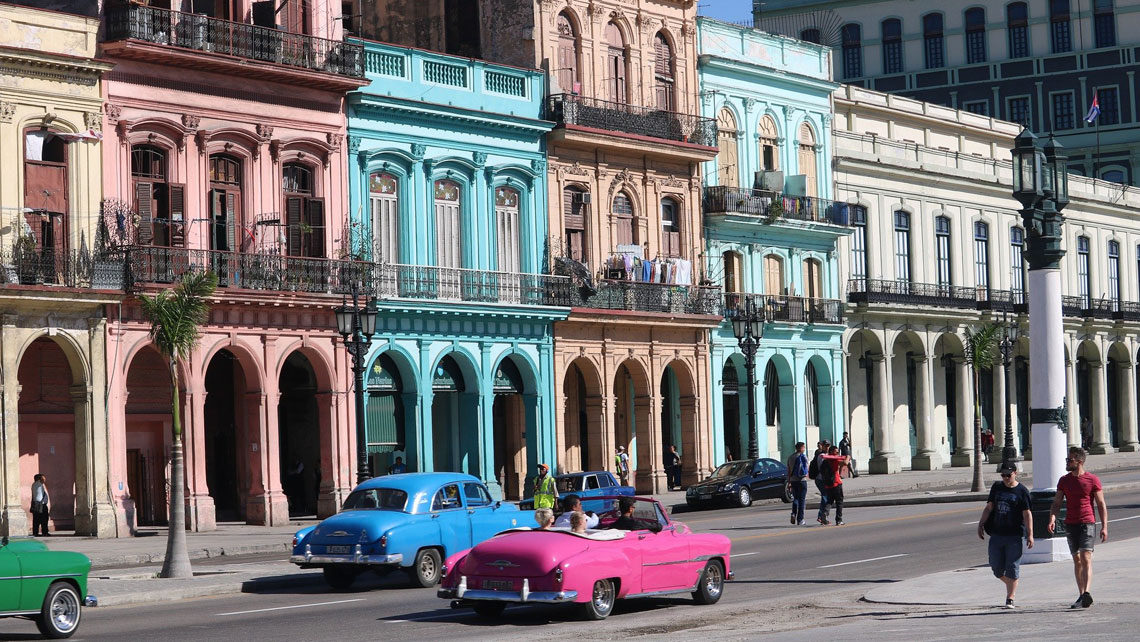 Vintage cars passing by colorful buildings in Havana, Cuba
